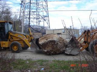 Trucks moving a giant boulder